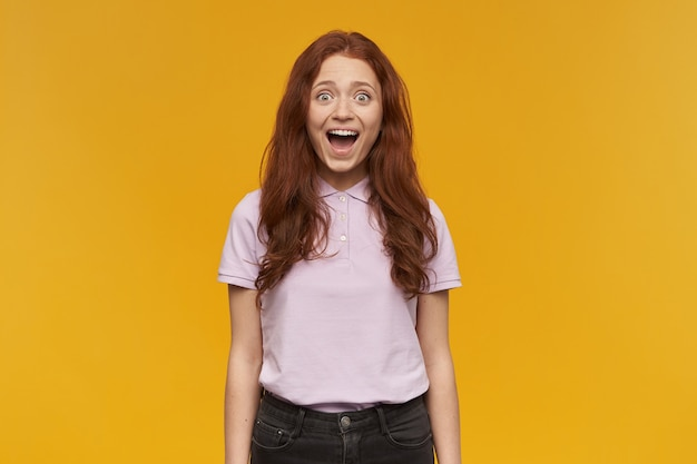 긴 생강 머리를 가진 흥분, 아름 다운 아가씨의 초상화. 분홍색 티셔츠를 입고. 사람과 감정 개념. 당신을 만나서 놀랐습니다. 오렌지 벽 위에 절연 무료 사진