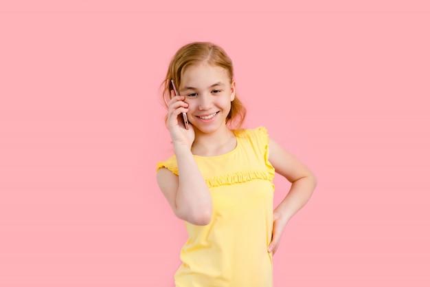 Портрет возбужденных красивая девушка подросток в желтой футболке, держа мобильный телефон, изолированных на розовом фоне