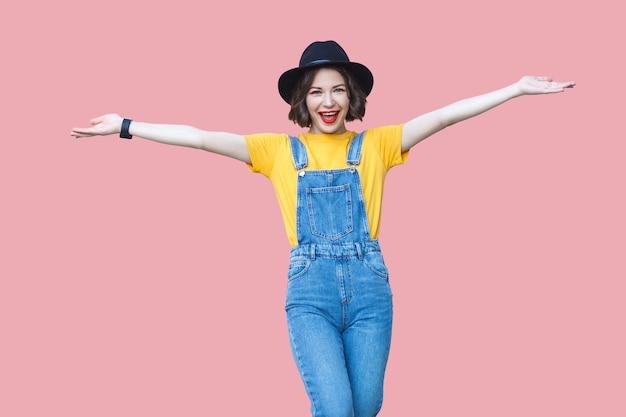 黄色のtシャツ、青いデニムのオーバーオール、メイク、腕を上げて立っている黒い帽子と歯を見せる笑顔でカメラを見ている興奮した美しい若い女性の肖像画。ピンクの背景にスタジオ撮影。
