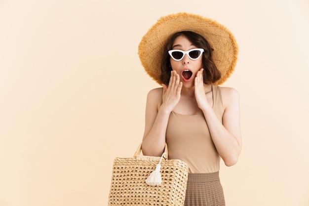 밀짚 모자와 선글라스를 쓴 흥분한 브루네트 여성의 초상화는 입을 벌리고 고립되어 놀라움을 표현합니다