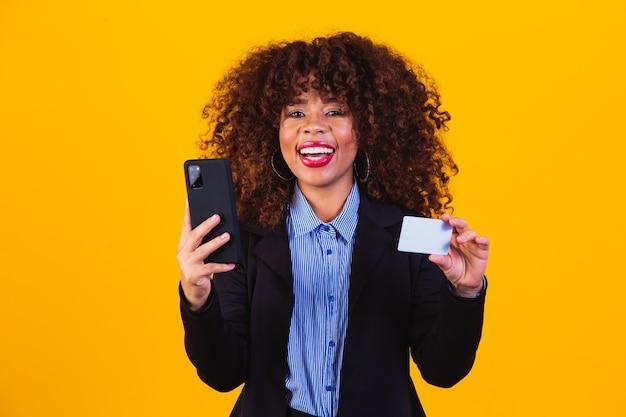 黄色の背景で隔離のクレジットカードを立って保持しながら携帯電話を見ている興奮したビジネス女性の肖像画。