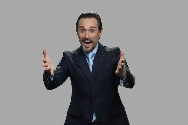手で身振りで示す興奮した実業家の肖像画。灰色の背景に大喜びの白人マネージャー。勝利と成功のコンセプト。