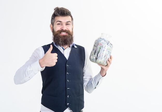 흥분한 사업가의 초상화는 돈과 돼지 저금통이 든 항아리를 들고 있습니다. 은행 광고. 돈 개념을 저장합니다. 은행 개념입니다. 사업가 쇼 기호가 좋습니다. 엄지손가락으로 사업가입니다.