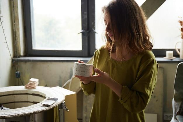 粘土製品を調べる興奮した陶芸家の肖像画。陶芸工房で働く女性陶芸家。陶器を作るプロセス。マスター陶芸家は彼女のスタジオで働いています