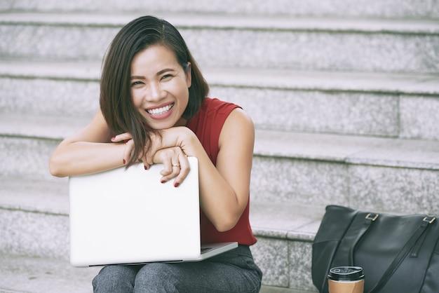 Портрет возбужденной очаровательной бизнес-леди, обнимая ее ноутбук, сидя на мраморной лестнице