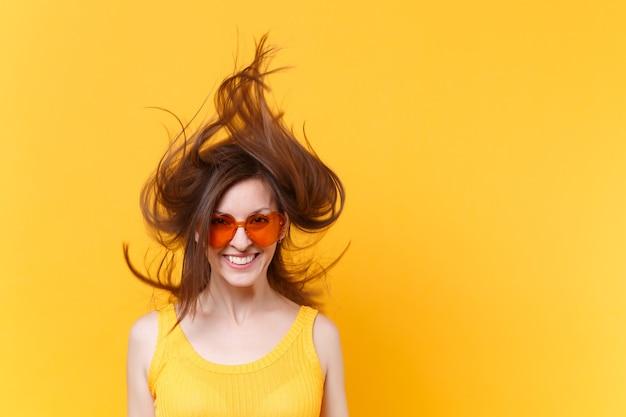 Портрет возбужденной веселой смеховой смешной комической женщины в оранжевых очках с развевающимися волосами копирует пространство, изолированное на желтом фоне. люди искренние эмоции, концепция образа жизни. рекламная площадка.