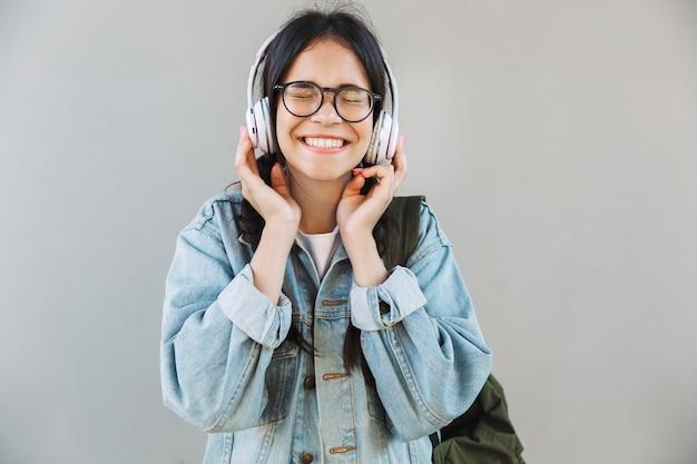 ヘッドフォンで音楽を聴いて灰色の壁の上に隔離された眼鏡を身に着けているデニムジャケットで興奮した陽気なかわいい女の子の肖像画。