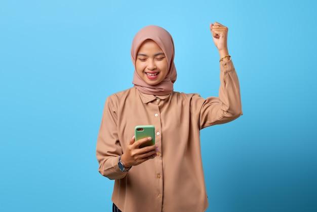 手持ちの携帯電話で勝利を祝う興奮した陽気な若いアジアの女性の肖像画