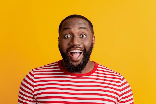 Портрет возбужденного сумасшедшего человека смотрит в камеру с открытым ртом на желтом фоне