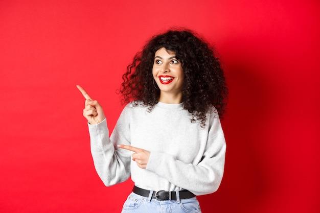 Портрет возбужденной кудрявой женщины с красными губами, смотрящей и указывающей налево на логотип, с удивленным лицом че ...