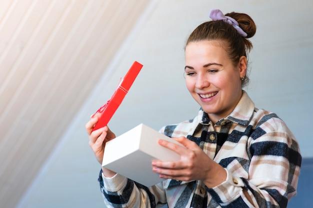 흥분된 귀여운 예쁜 여자의 초상화는 여는 손에 선물 상자를 들고. 젊은 아름 다운 여자