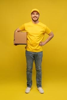 黄色の壁の上に分離された紙箱を保持している黄色の制服を着た興奮した配達人の肖像画