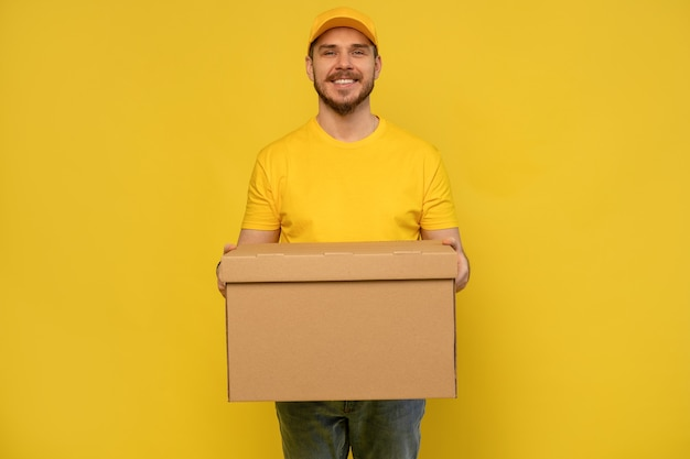 黄色の壁の上に分離された紙箱を保持している黄色の制服を着た興奮した配達人の肖像画 Premium写真