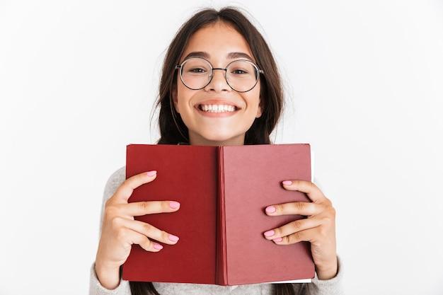 本を読んで保持している白い壁の上に分離された興奮した感情的な若い女子高生の肖像画