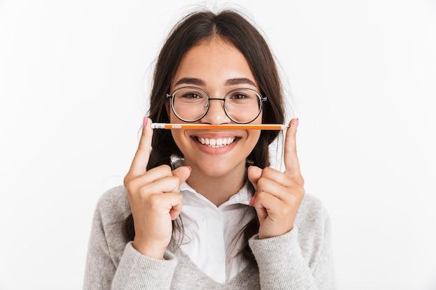 鉛筆を保持している白い壁の上に分離された興奮した感情的な若い女子高生の肖像画
