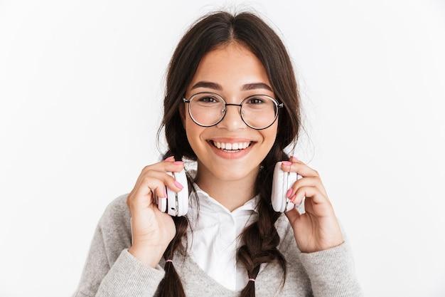 ヘッドフォンポーズで白い壁に隔離された興奮した感情的な若い女子高生の肖像画