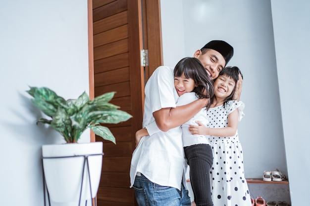 Портрет взволнованного отца обнимает и обнимает своих детей во время празднования ид мубарак вместе