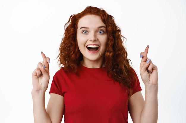 Портрет взволнованной рыжей девушки, задыхающейся от изумления, скрестив пальцы на удачу и глядя, загадывая желание, ожидая хороших новостей, желая выиграть, белая стена