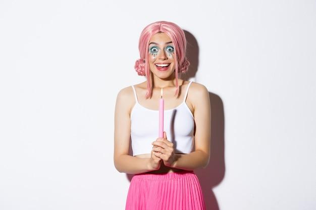 Портрет взволнованной девушки, празднующей хеллоуин в костюме феи, с ярким макияжем и розовым париком, держащей свечу и улыбающейся.