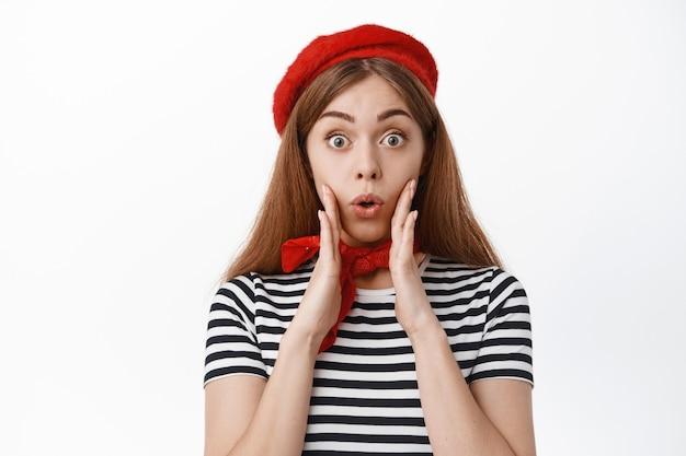 フランスのベレー帽で興奮した少女の肖像画、驚いて驚いて見つめ、口の近くで手を握り、あえぎ、すごい、白い壁に立って