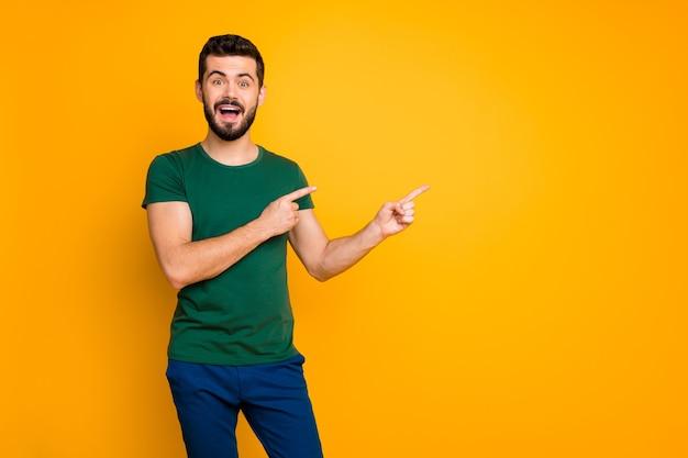 Портрет возбужденного промоутера парня указывает на copyspace указательного пальца