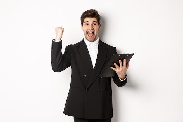 Портрет возбужденного красивого бизнесмена в черном костюме, держащего буфер обмена и делающего кулачковый насос, достигает цели и радуется, стоя на белом фоне.
