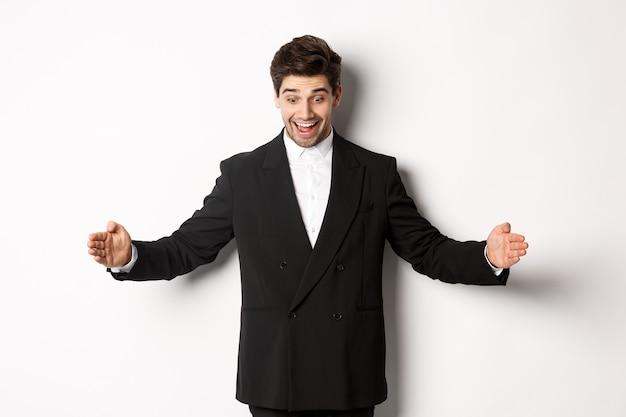 スーツを着て興奮しているハンサムな男の肖像画、コピースペースで大きなオブジェクトを形作り、驚いて笑って、何かを持って、白い背景の上に立っています。