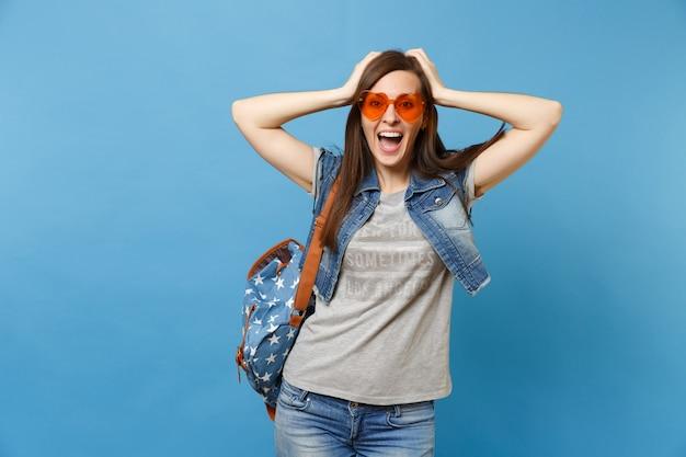 青い背景で隔離の頭にしがみついているデニムの服オレンジ色のハートのメガネのバックパックを持つ興奮した幸せな楽しい女性学生の肖像画。高校での教育。広告用のスペースをコピーします。