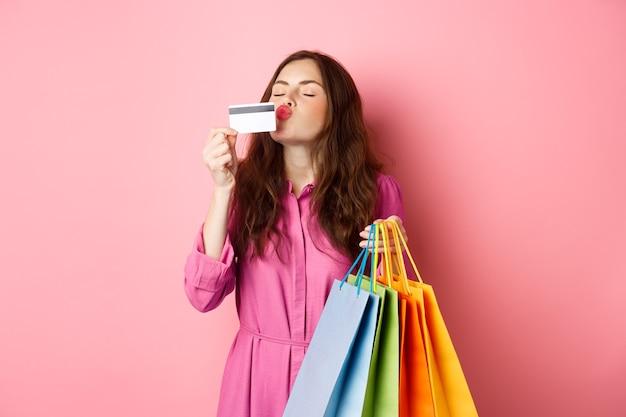 興奮した幸せな買い物中毒者、買い物袋を持ってプラスチックのクレジットカードにキスをし、驚いて笑って、ピンクの壁に立っている女性の肖像画。