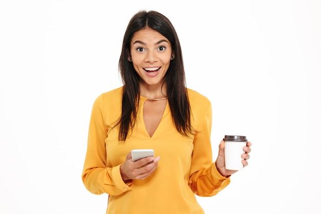 Портрет взволнован счастливой женщины, держащей мобильный телефон