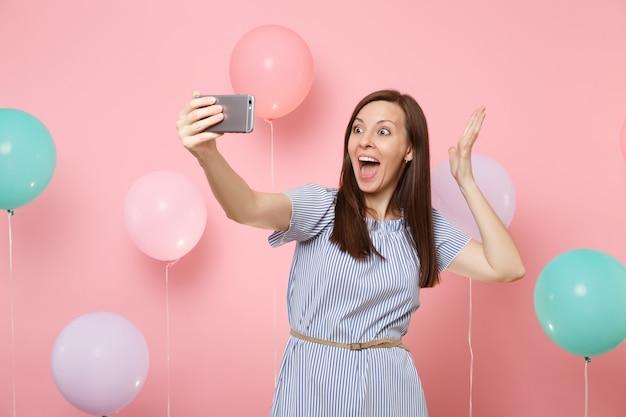 カラフルな気球でパステルピンクの背景に手を広げて携帯電話でselfieをしている青いドレスで興奮した幸せな女性の肖像画。誕生日の休日のパーティーの人々の誠実な感情の概念。