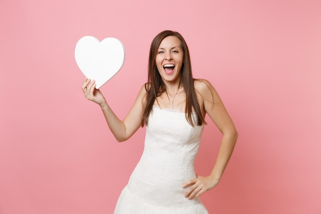 Портрет возбужденной счастливой женщины в элегантном белом платье, стоящей с белым сердцем с копией пространства