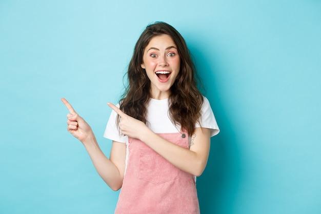 어둡고 반짝이는 곱슬머리를 한 흥분한 행복한 여성의 초상화, 매료되어 웃고, 로고 배너에 왼쪽 손가락을 가리키는 것은 파란색 배경 위에 서 있는 광고를 보여줍니다.