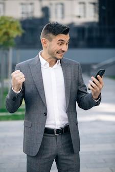 Портрет взволнованного человека, читающего хорошие новости на смартфоне на открытом воздухе