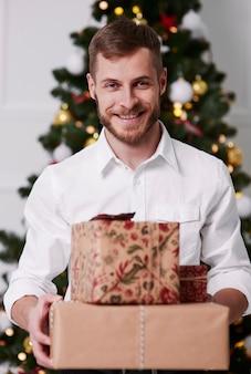 Портрет возбужденного мужчины со стопкой подарков