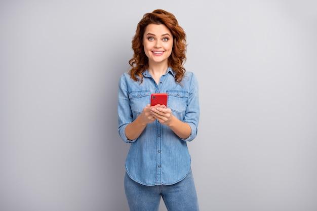 興奮したポジティブな陽気な女性の肖像画は携帯電話を使用してテキストメッセージを入力してブログの投稿を楽しむ