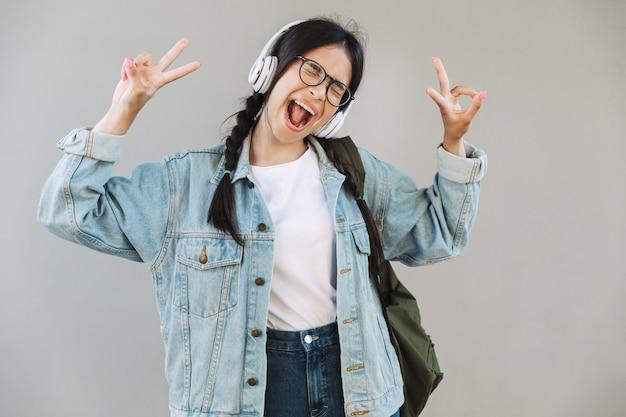 平和を示すヘッドフォンダンスで音楽を聴いて灰色の壁の上に隔離された眼鏡を身に着けているデニムジャケットで興奮したかわいい女の子の肖像画。