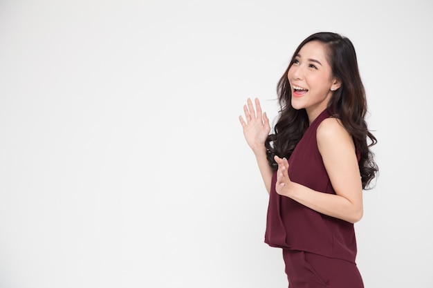 白で隔離される赤いドレスで立っている興奮して叫んでいる若いアジア女性の肖像画