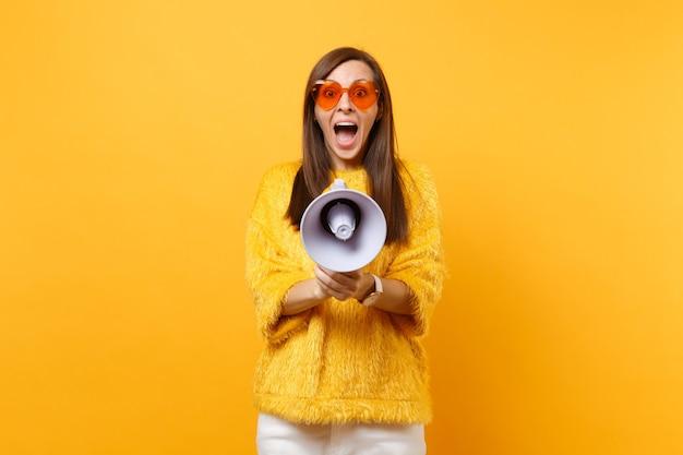 明るい黄色の背景に分離されたメガホンで叫んでいる毛皮のセーターオレンジ色のハートの眼鏡で興奮したショックを受けた若い女性の肖像画。人々の誠実な感情のライフスタイルの概念。広告エリア。