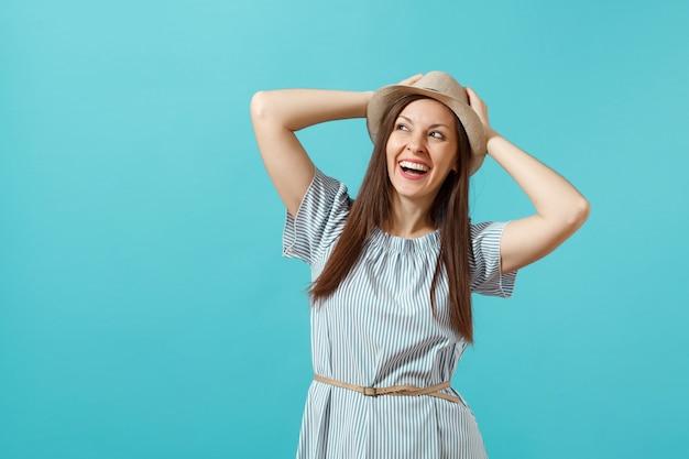 ドレス、わらの夏の帽子を身に着けている興奮した笑顔の若いエレガントな女性の肖像画は、頭に手を置き、青い背景で隔離のスペースをコピーします。人々の誠実な感情、ライフスタイルのコンセプト。広告エリア。