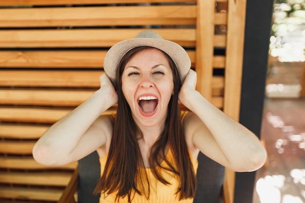Портрет возбужденной улыбающейся молодой женщины в соломенной летней шляпе, желтая рубашка положила руки на голову на деревянной стене в уличном летнем кафе
