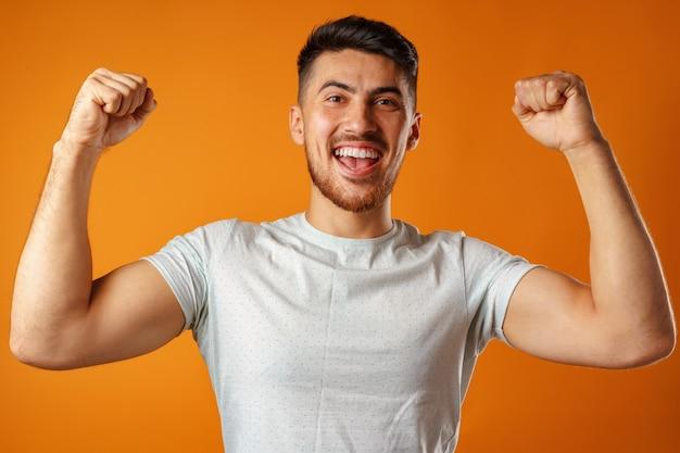 興奮した、成功した男の手を上げる肖像画