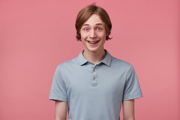 치아에 교정기와 흥분된 놀란 기쁜 파란 눈 깔끔하게 빗질 한 젊은 남자의 초상화는 행복하게 폴로 티셔츠를 입고 분홍색 배경 위에 고립 된 행복을 느낍니다.