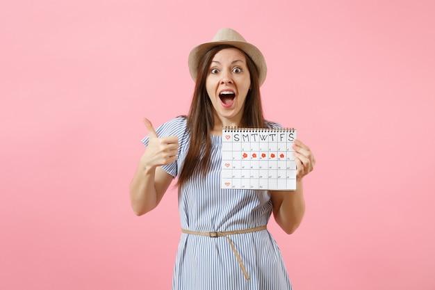 青いドレス、明るいトレンドのピンクの背景で隔離の月経日をチェックするための期間カレンダーを保持している興奮した女性の肖像画。医療、ヘルスケア、婦人科の概念。コピースペース