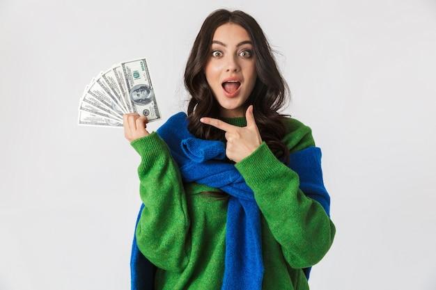 白で孤立して立っている間、ドルのお金のファンを保持しているカジュアルな服を着て興奮した女性の肖像画