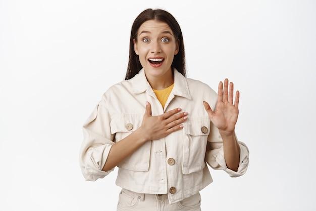 Портрет взволнованной женщины выглядят пораженными, поднимая руку и кладя руку на грудь, говоря правду, честное слово, приветствуя, представляясь, стоя в повседневной одежде на белом.