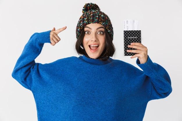 Портрет возбужденной женщины в зимней шапке, держащей паспорт и проездные билеты стоя, изолированную на белом