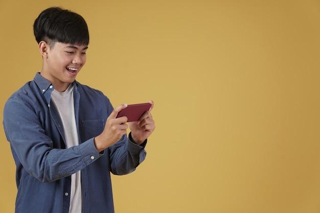 흥분된 젊은 아시아 남자의 초상화는 부담없이 고립 된 스마트 폰에서 비디오 게임을 입고