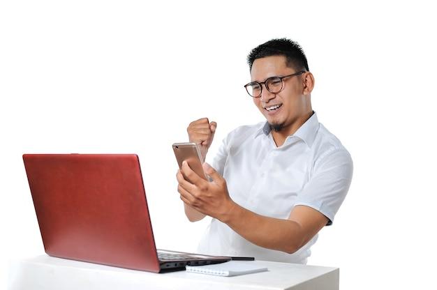 책상 위에 노트북 근처에 앉아 있는 흥분한 젊은 아시아 남성의 초상화는 온라인 프리랜서로 작업을 성공적으로 완료하고 흰색으로 격리된 지불을 받았습니다.