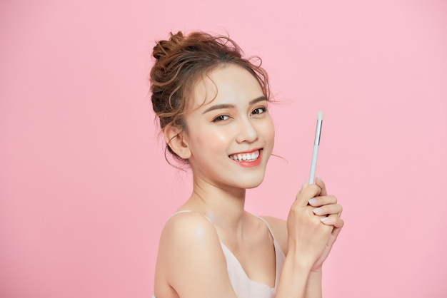 브러시를 들고 분홍색 배경 위에 화장을 하는 흥분한 젊은 아시아 여성의 초상화.